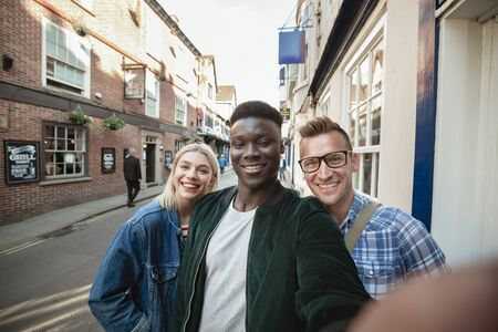 A selfie shot of two men and one woman on a city street. They are smiling at the camera.