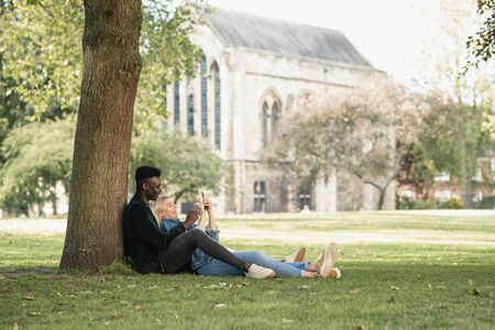 A man and woman sitting in a park against a tree. The woman is sitting in between the man's legs while showing him something on her mobile phone.