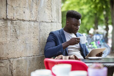 Businessman sitting down at an outdoor table in a city while drinking a hot drink and looking at his digital tablet. Stockfoto