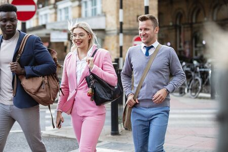 A businesswoman walking with two businessmen home from work through the city.