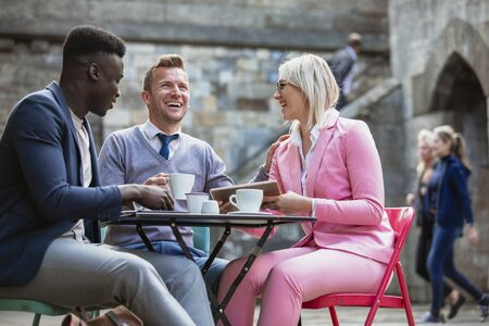 Two businessmen and a businesswoman sitting at an outdoor table in a city having a hot drink while laughing at something on a digital tablet. One man is touching the woman on the shoulder.