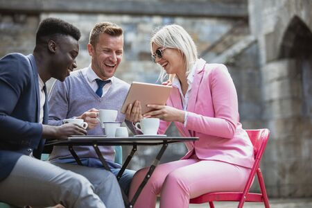 Two businessmen and a businesswoman sitting at an outdoor table in a city having a hot drink while laughing at something on a digital tablet.