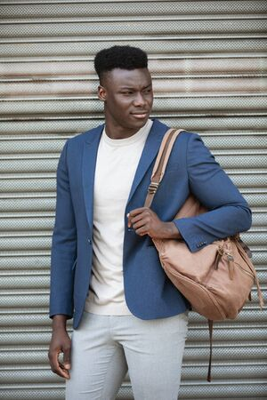 Three quarter length shot of a businessman standing in front of a shutter in the street. He is wearing smart casual clothing while holding a satchel over his shoulder. He is looking to his side.