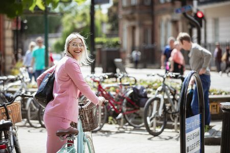 A businesswoman looking back at the camera while holding onto a bicycle, ready to ride it to work. Stockfoto