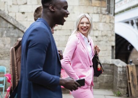 A group of businesspeople walking home from work together. The main focus is on one businesswoman smiling and laughing at the two other men. Stockfoto