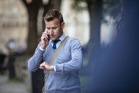 Businessman on his way to work while talking on the phone and checking the time.
