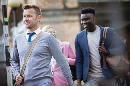 Businesspeople walking home after a day of work. The main focus is on one man walking in front of people. Stockfoto
