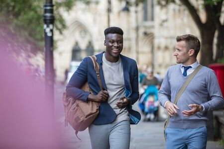 Two businessmen walking to work through the city.