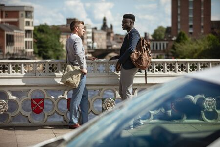 Two businessmen having a chat on a bridge in York. They are facing each other.