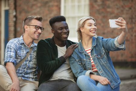 A woman taking a selfie with two other men while sitting down on a bench.