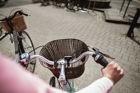 Over the shoulder view of a woman riding a bicycle. The main focus is on the front of the bicycle and its basket. Stockfoto