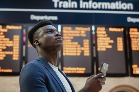 A businessman looking up in a train station while holding his mobile phone. The arrival departure board is behind him.