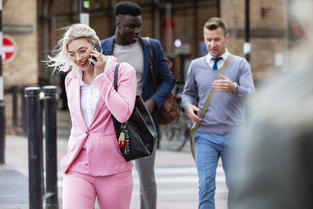 Businesspeople walking home after a day of work. The main focus is on one businesswoman walking in front of people while talking on her mobile phone. Stockfoto