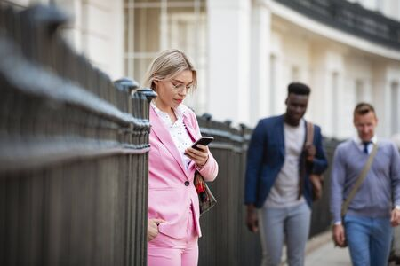 Businesswoman standing on a city street while using her phone. Two businessmen are about to walk past. Stockfoto