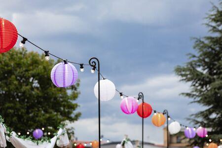 A wide shot of paper lanterns hanging up alongside a set of string lights at a garden party.
