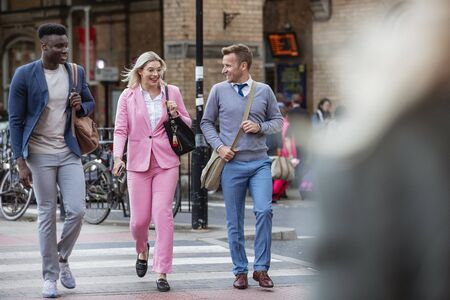 A businesswoman walking with two businessmen home from work through the city. They are walking over a zebra crossing.