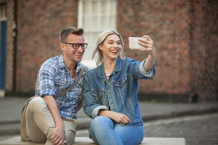 A woman taking a selfie with a man while sitting down on a bench.