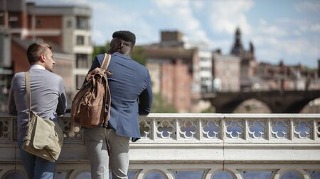 Two businessmen talking while leaning on a bridge in York.They have their backs to the camera.