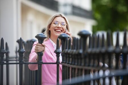 A businesswoman laughing while talking on her mobile phone. She is holding onto iron fencing. Stockfoto