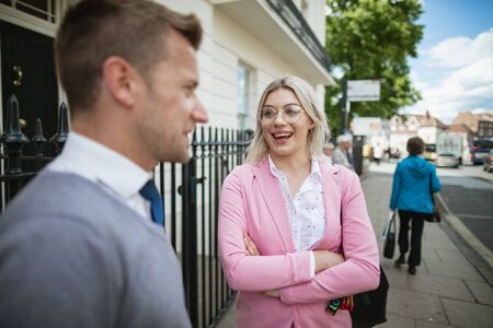 A close-up of two businesspeople waiting for a bus on a city street. Stockfoto