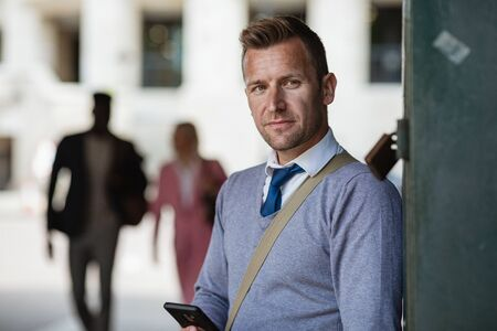 A businessman leaning against a wall while looking away from the camera with a mobile phone in his hand.