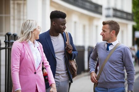 Two businessmen and one businesswoman walking to work while having a discussion. Stockfoto