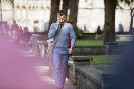 Businessman walking to work while talking on the phone. Stockfoto