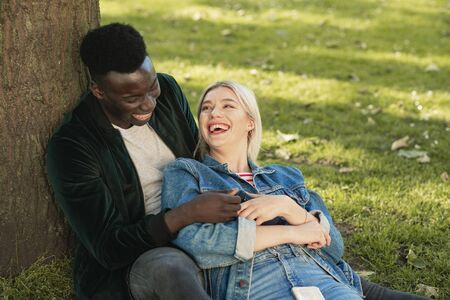 A man and woman sitting in a park against a tree. The man is holding her as she sits in between his legs. They are looking at each other while laughing. 写真素材