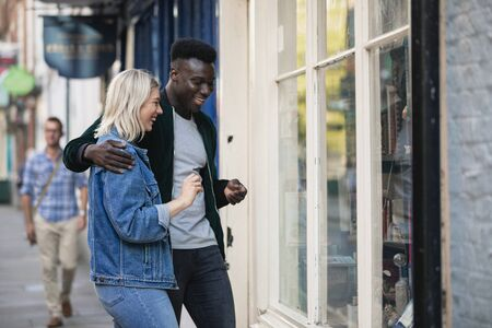 A man and woman standing outside a shop window together, he has his arm around her. Stockfoto