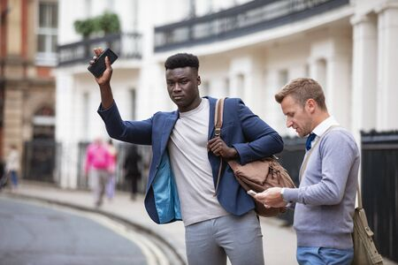 Two men trying to catch a taxi to get to work. One is trying to track one down while the other man browses on his phone.