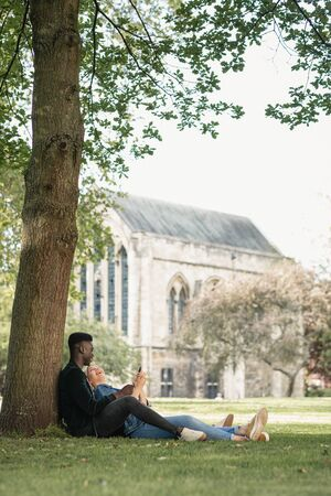 A man and woman sitting in a park against a tree. The woman is sitting in between the mans legs while showing him something on her mobile phone. The woman is looking up at the man and laughing. Stockfoto