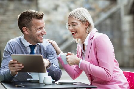 Two businesspeople sitting down and laughing at something on a digital tablet. The businesswoman is holding a hot drink and has her hand on the businessmans shoulder while he holds the tablet. Stockfoto