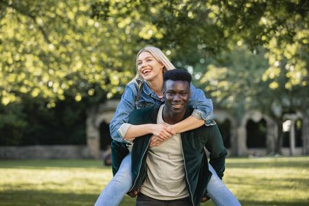 A man giving a woman a piggyback lift through a park. They are both smiling.
