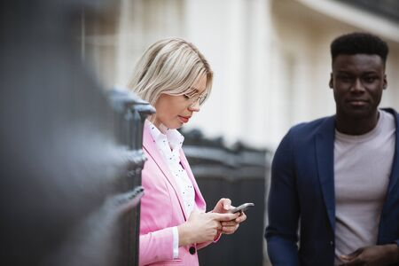 A close-up of a woman standing against an iron gate while texting on her mobile phone. A man is about to walk past her. Stockfoto