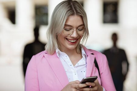 A businesswoman looking down at her phone and typing while smiling.