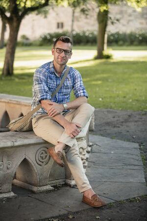 A man wearing casual clothing, sitting on a stone bench in the park. Archivio Fotografico - 133442456