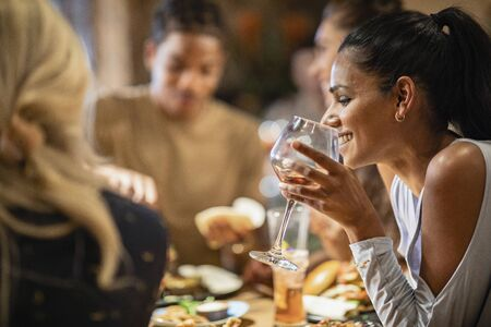 A group of friends having a meal at a restaurant together. The main focus is a Sri Lankan woman drinking from a wineglass.