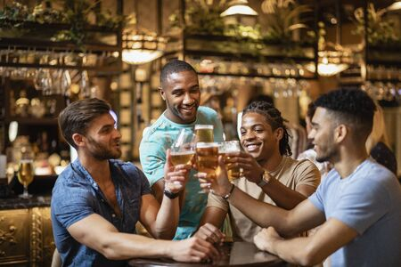 A group of male friends having a celebratory toast together with pints of beer.