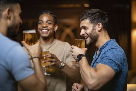 A group of male friends having a pint of beer together in a bar. Stockfoto