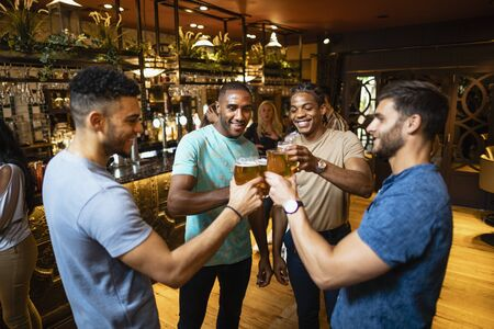 A group of male friends having a celebratory toast together in a bar.