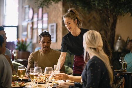 A waitress serving a meal to customers at a restaurant in Newcastle-Upon-Tyne.