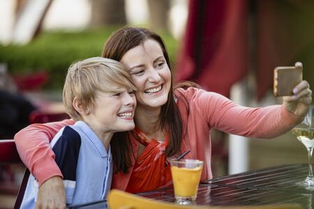 Mother and son taking a selfie together outdoors at bar in Newcastle Upon Tyne.