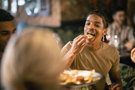 A group of friends eating a meal at a restaurant. The main focus is on a mixed race man eating food. Stockfoto