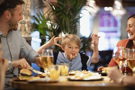 A family having a meal at a restaurant. A young boy is making them all laugh by making a face using food. Stockfoto