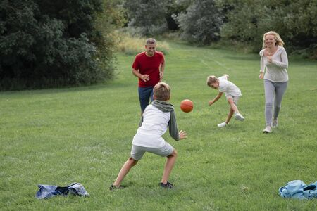 A shot of a family playing football together on a field.