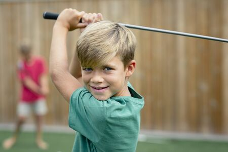 A front view shot of a young boy golfer smiling and looking at the camera, he is holding a golf club.