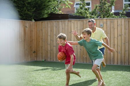 A shot of a family of boys playing with a basketball in the back yard. Stockfoto