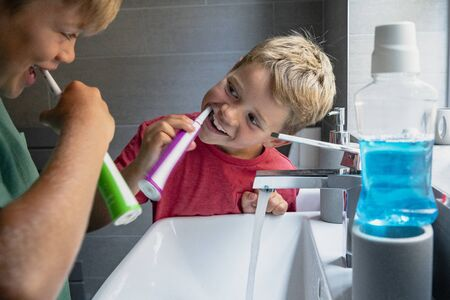 A side view shot of two young boys brushing their teeth together at the sink. Stockfoto