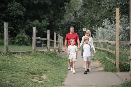 A front-view shot of a happy family wearing casual clothing walking down a footpath in a tranquil scene. Stockfoto