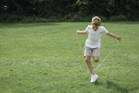 A front view portrait shot of a young boy playing with a skipping rope